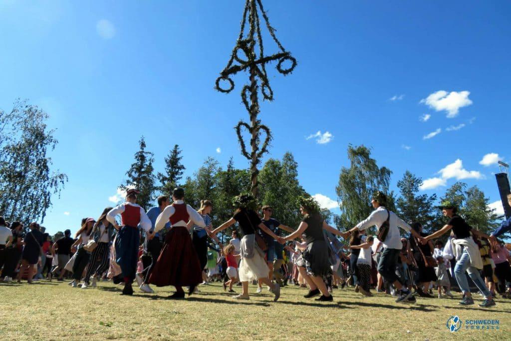 Schweden tanzen zu Midsommar um eine Maistange
